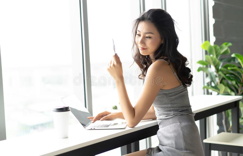 Young attractive caucasian Asian woman holding credit card and u stock image