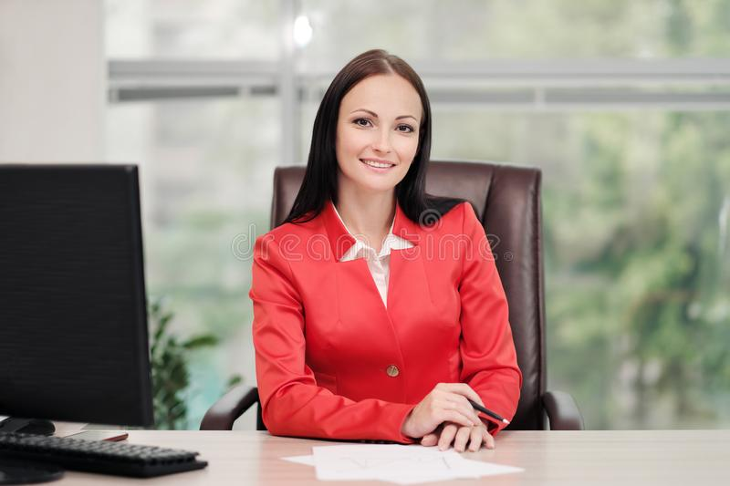 A young attractive Caucasian blond woman in a red business suit sits at a desk in a bright office. Portrait of a royalty free stock photo