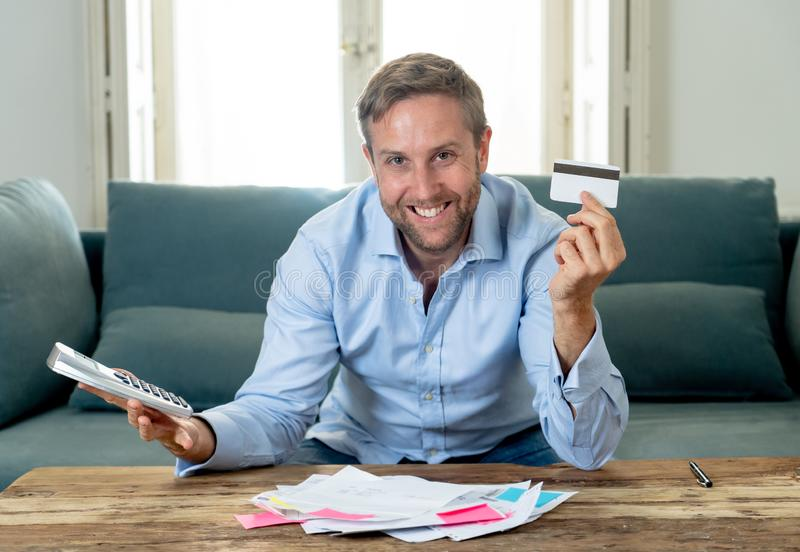 Attractive successful business man with credit card accounting finance Happy free of debts. Young attractive caucasian business man accounting costs, charges royalty free stock image