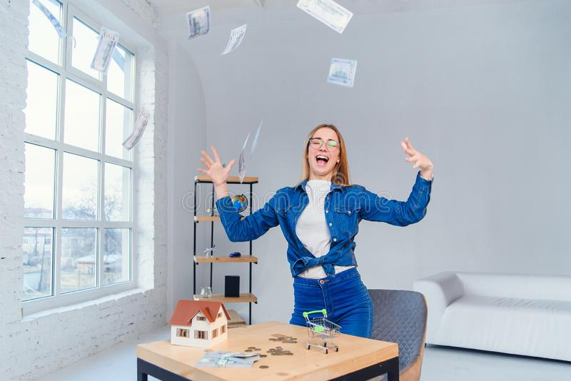 Young attractive caucasian girl in eyeglasses scatters us dollar banknotes on a white room background. Business and. Young attractive caucasian girl in stock photography