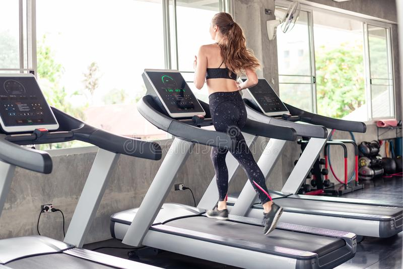 Young attractive caucasian woman doing cardio training workout in gym .Healthy sporty girl running on treadmill at panoramic stock photography