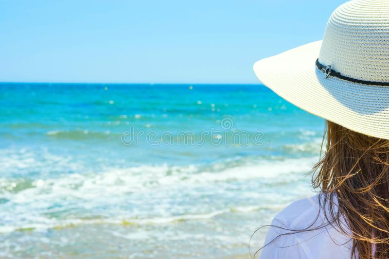 Young Attractive Caucasian Woman with Long Chestnut Hair in Hat Stands with Back On Sand Beach Looks at Turquoise Sea Horizon. On Blue Sky Background royalty free stock photography