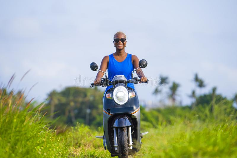 Young attractive tourist afro American black woman riding motorbike happy in beautiful Asia countryside along green rice fields s. Young attractive and cheerful stock photography