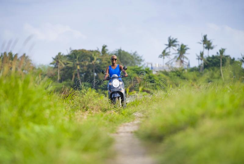 Young attractive tourist afro American black woman riding motorbike happy in beautiful Asia countryside along green rice fields s. Young attractive and cheerful royalty free stock photo