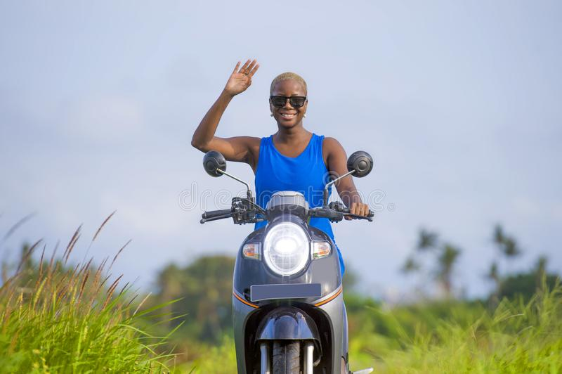 Young attractive tourist afro American black woman riding motorbike happy in beautiful Asia countryside along green rice fields s. Young attractive and cheerful royalty free stock image