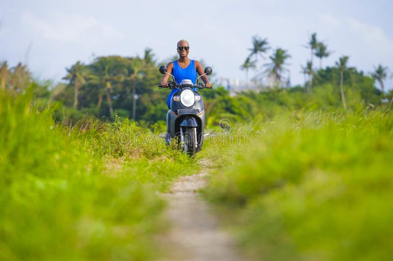 Young attractive tourist afro American black woman riding motorbike happy in beautiful Asia countryside along green rice fields s. Young attractive and cheerful stock photo