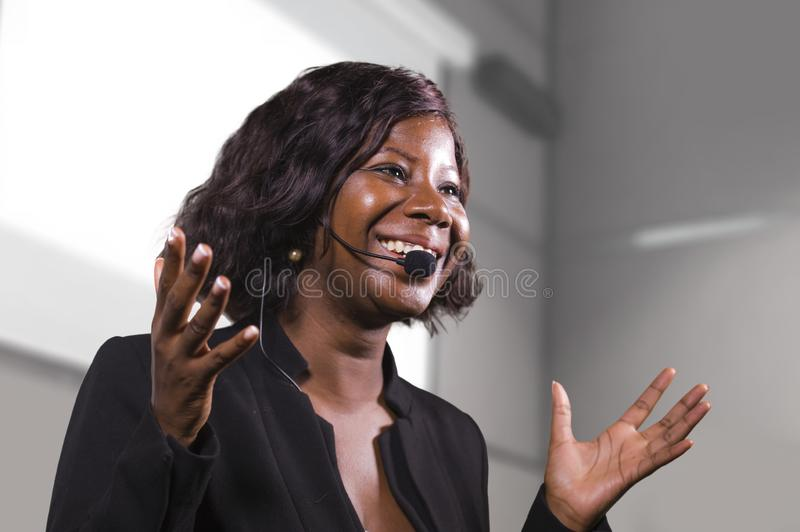 Young attractive and confident black African American business woman with headset speaking in auditorium at corporate training royalty free stock image