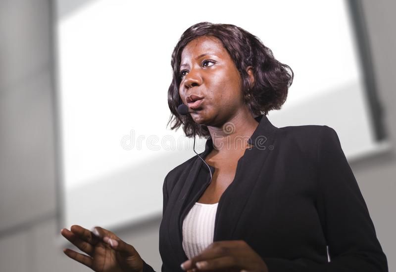 Young attractive and confident black African American business woman with headset speaking in auditorium at corporate training. Event or seminar giving royalty free stock photos