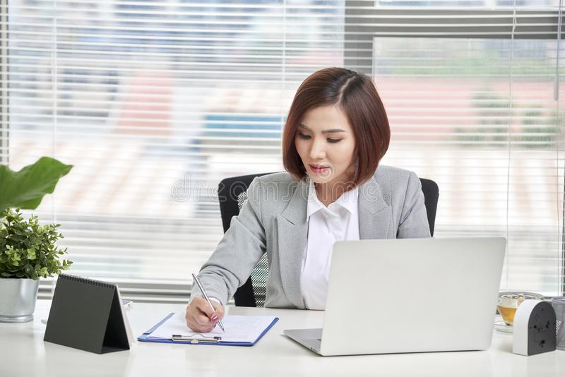 Young, attractive and confident business woman working in office.  stock images
