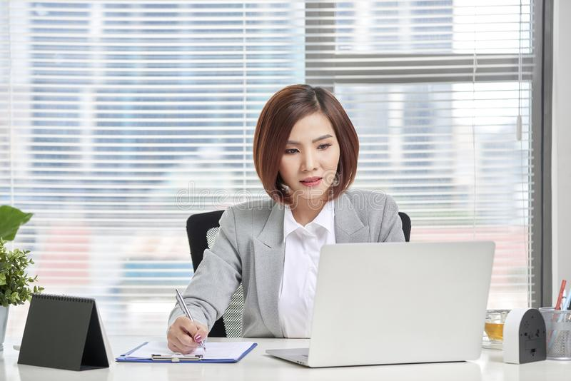 Young, attractive and confident business woman working in office stock image