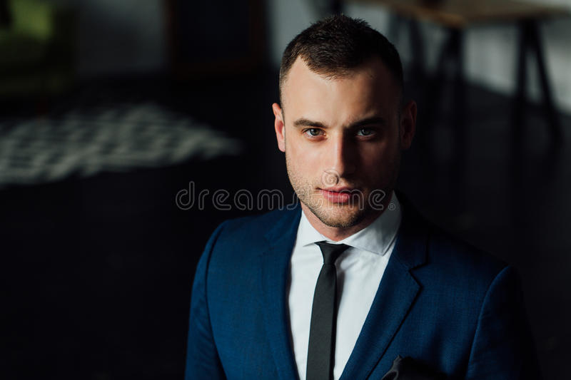 Young attractive and confident businessman in blue suit and black tie. stock images
