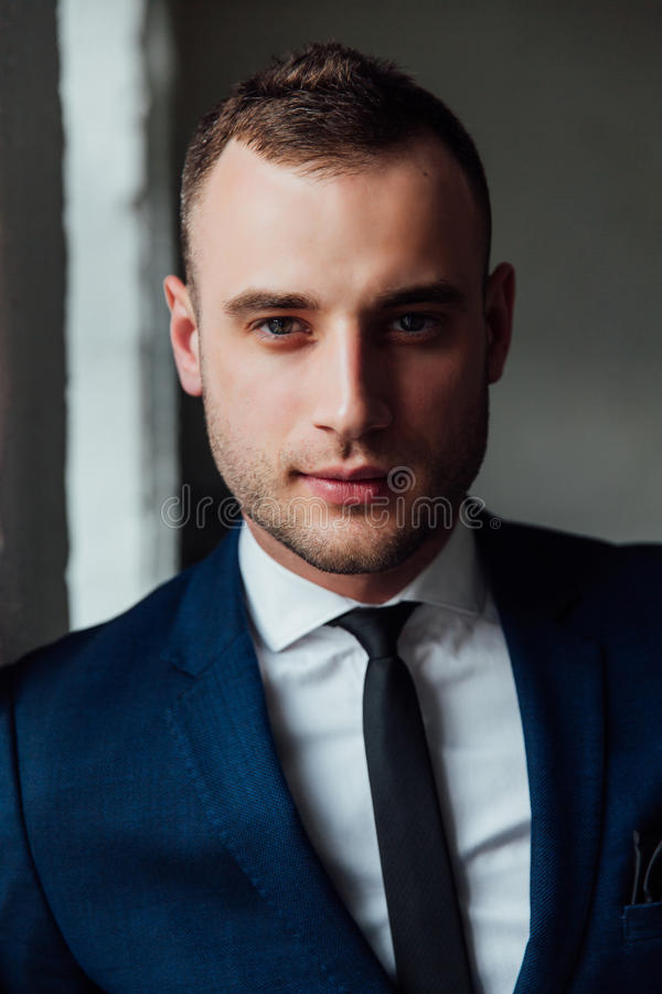 Young attractive and confident businessman in blue suit and black tie. Close-up portrait, looking at the frame. Headshot. An intriguing sight. Playful and royalty free stock photo