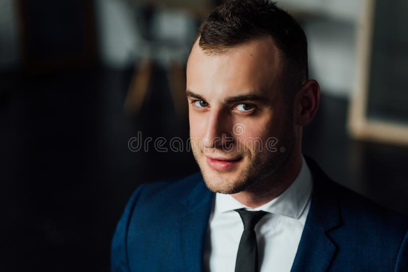Young attractive and confident businessman in blue suit and black tie. royalty free stock image