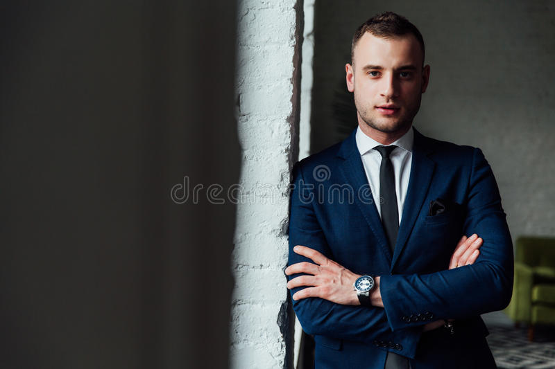Young attractive and confident businessman in blue suit and black tie. royalty free stock photos