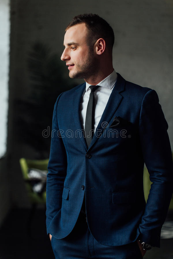 Young attractive and confident businessman in blue suit and black tie. stock photo