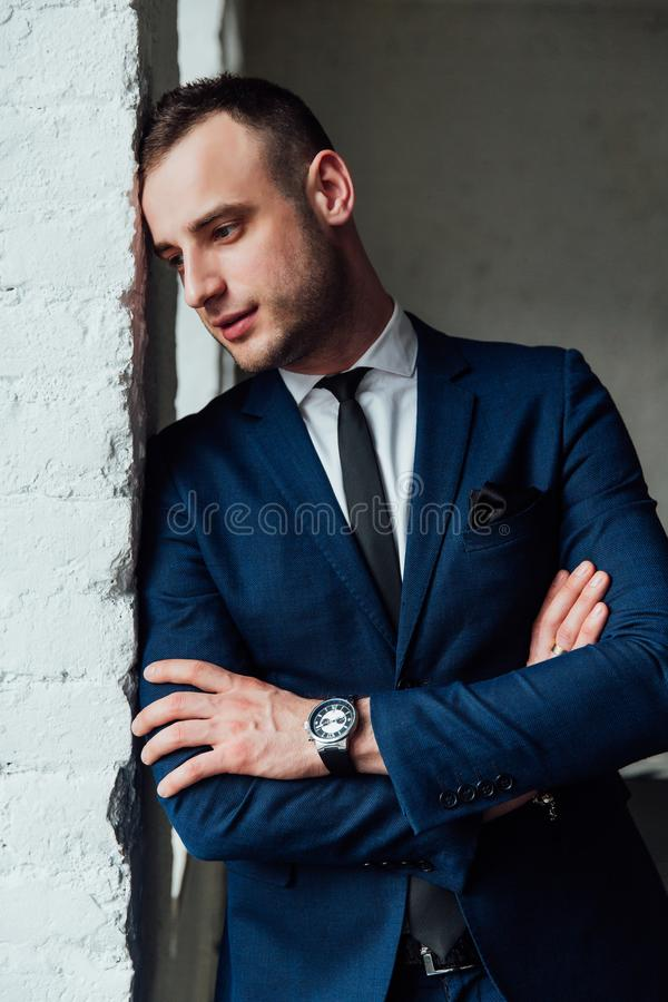 Young attractive and confident businessman in blue suit and black tie. stock photos