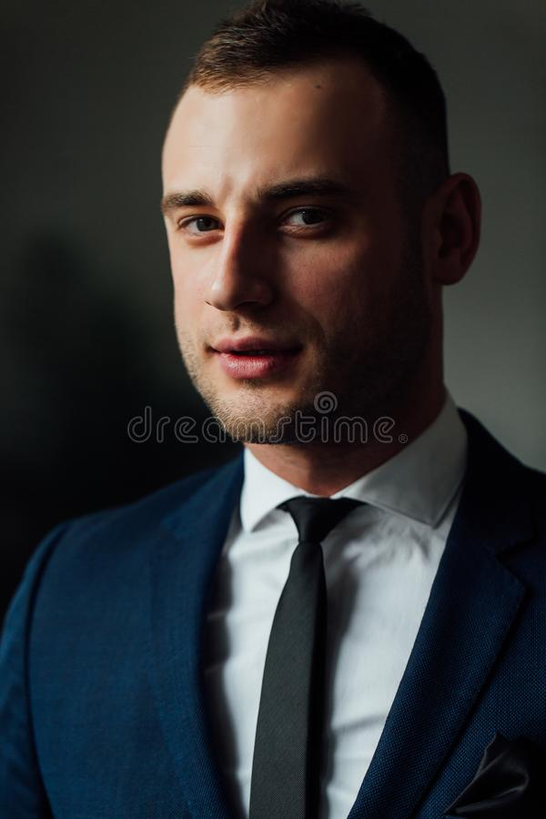 Young attractive and confident businessman in blue suit and black tie. royalty free stock photography