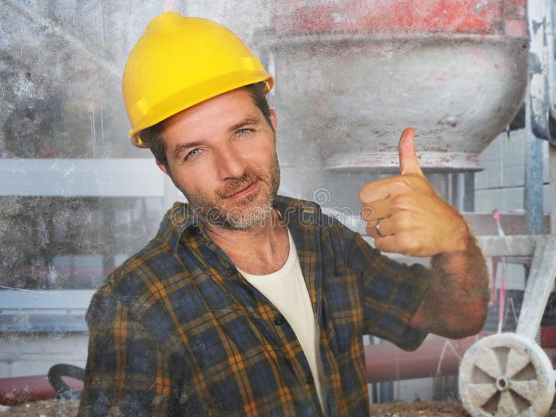 Young attractive and confident contractor or construction worker man with builder safety helmet posing corporate smiling cheerful stock image