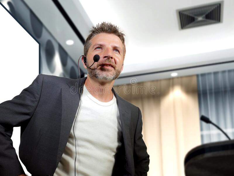 Young attractive and confident successful businessman with headset speaking at corporate company coaching and training at stock image