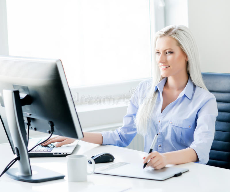 Young, attractive and confident woman in the office. Young, attractive and confident woman working in office. Retoucher editing photos royalty free stock photos