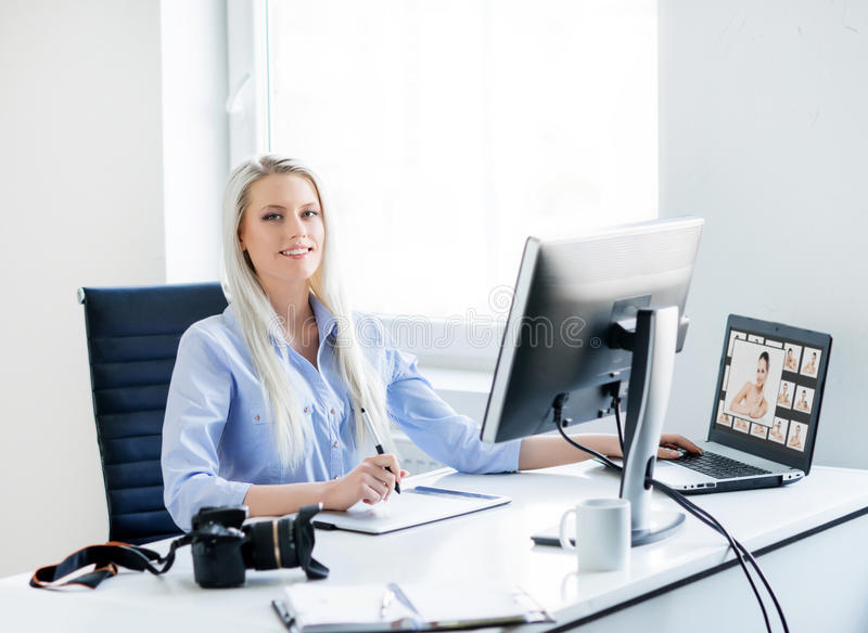 Young, attractive and confident woman working in office. Young, attractive and confident women working in office. Retoucher editing photos royalty free stock photo