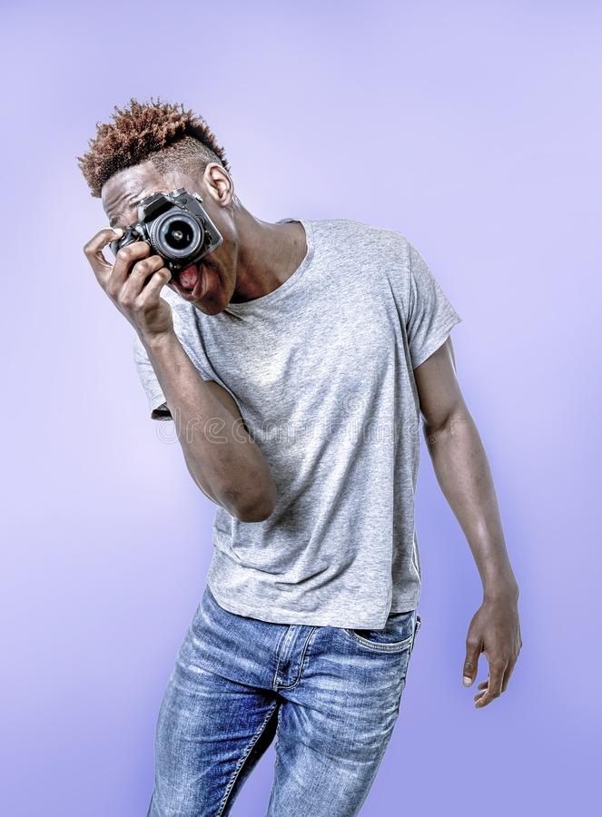 Young attractive and cool happy black afro American man holding digital reflex photo camera smiling excited background stock images