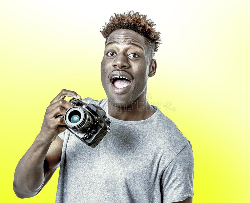 Young attractive and cool happy black afro American man holding digital reflex photo camera smiling excited on yellow bac stock image