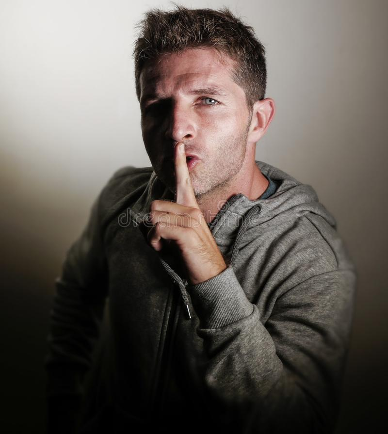 Young attractive and cool man with finger on lips in silence and shut up hand on mouth gesture on isolated background in dramatic. Studio light in censorship stock image