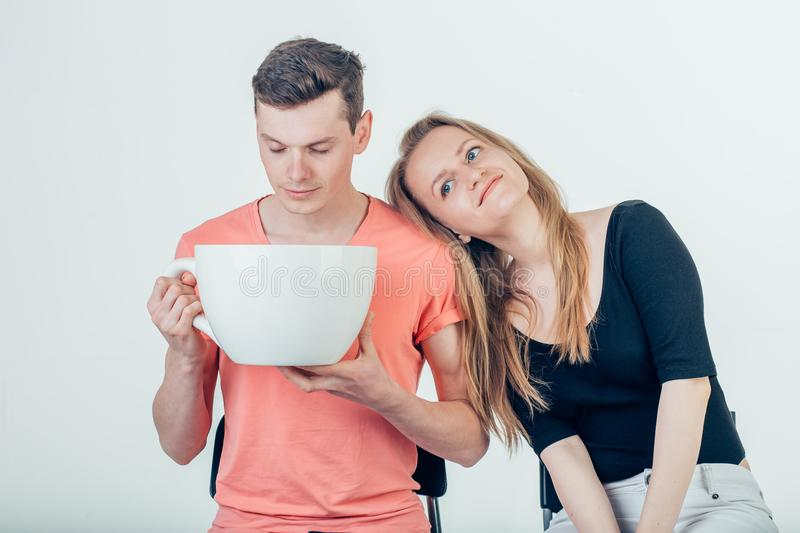 Young attractive couple on date in coffee shop with big coffee cup stock photo