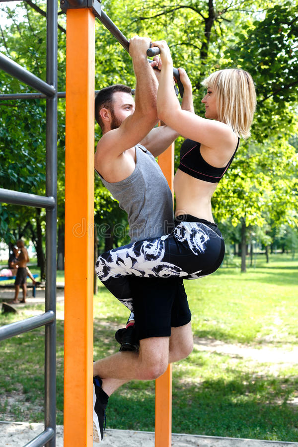 Young attractive couple doing pull-ups exercises on crossbar in. A parrk at summer day. Blonde girl hanging on bearded man stock images
