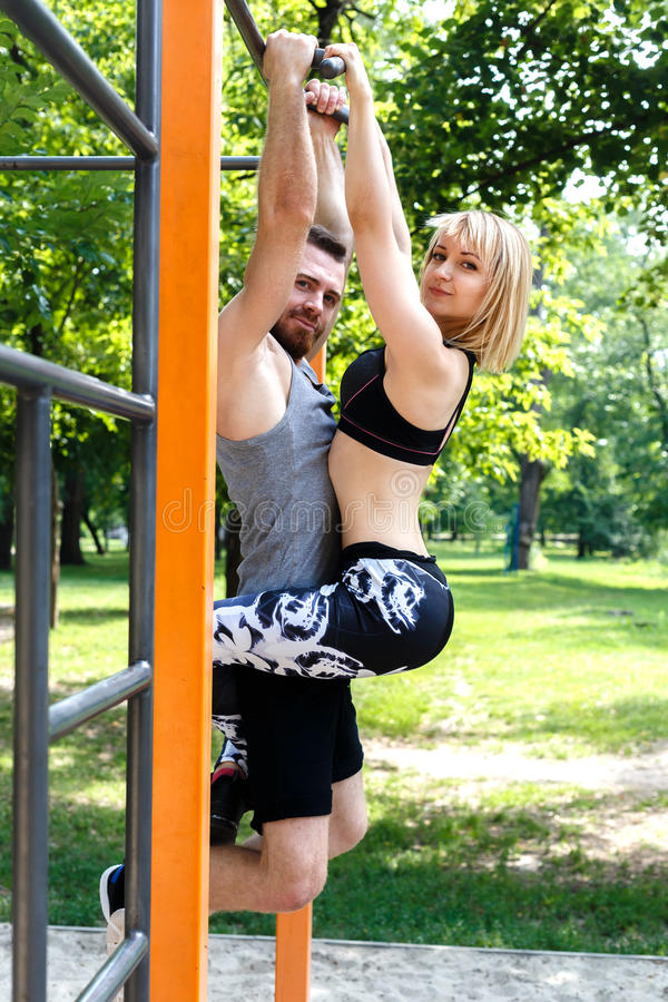 Young attractive couple doing pull-ups exercises on crossbar in. A parrk at summer day. Blonde girl hanging on bearded man royalty free stock images