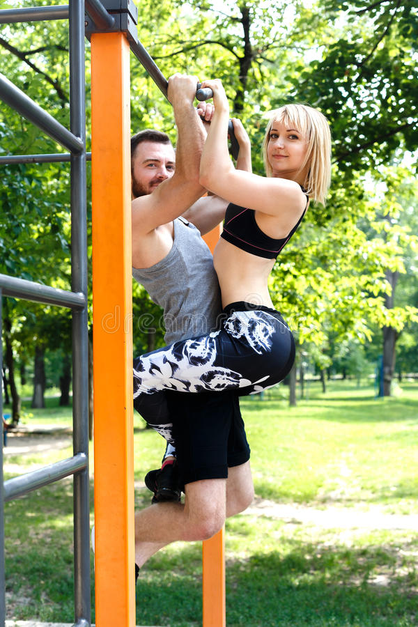 Young attractive couple doing pull-ups exercises on crossbar in. A parrk at summer day. Blonde girl hanging on bearded man royalty free stock image