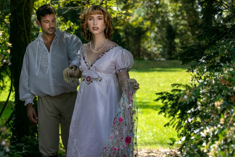 Young attractive couple dressed in vintage clothing walk through garden holding hands. royalty free stock photography