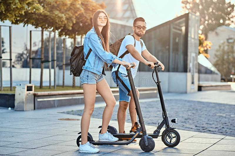 Young couple is enjoying electro scooter`s riding. Young attractive couple is enjoying nice summer day while riding their own electro scooters stock photo