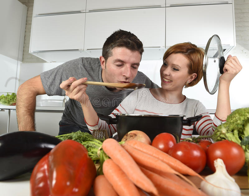 Young attractive couple at home kitchen with man tasting vegetable stew cooked by her wife smiling happy stock photo