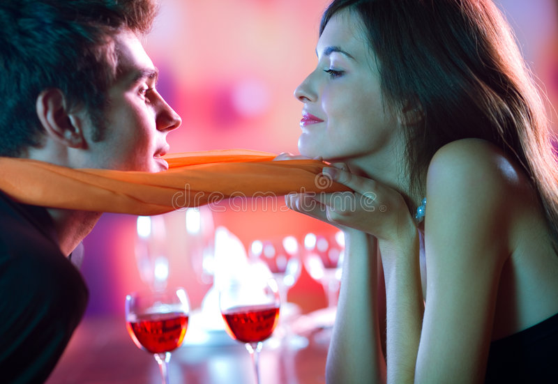 Young attractive couple kissing in restaurant, celebrating royalty free stock photo