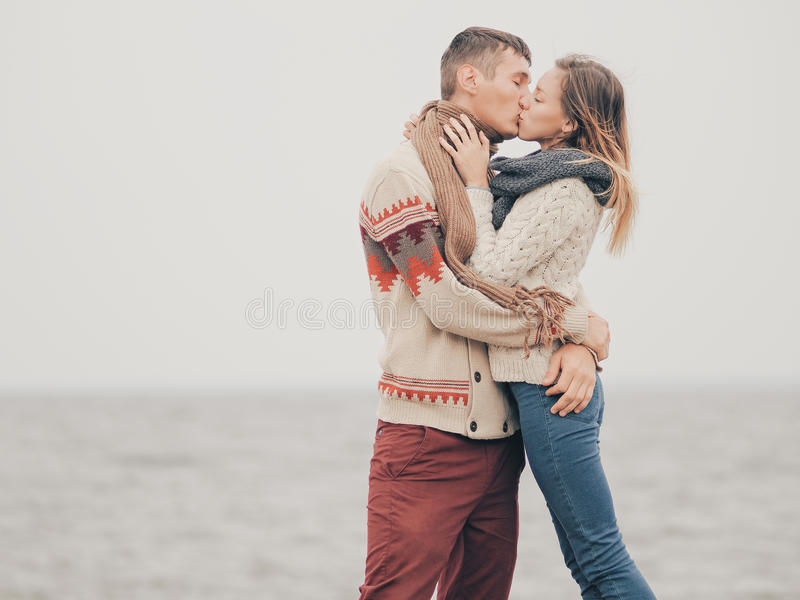 Young attractive couple in knitted sweaters on a cliff on sea shore. Kissing, creative toning stock image