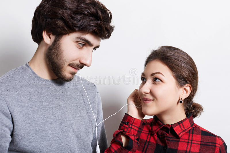 Young attractive couple listening to music with the same pair of earphones looking at each other with love isolated white backgrou stock photography