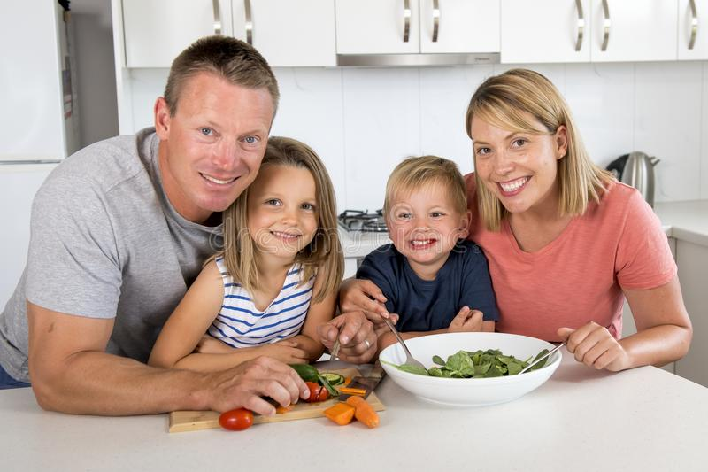 Young attractive couple mother and father preparing salad together with little son and young beautiful daughter in healthy vegetab royalty free stock image