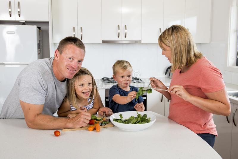 Young attractive couple mother and father preparing salad together with little son and young beautiful daughter in healthy vegetab stock photo