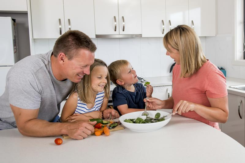 Young attractive couple mother and father preparing salad together with little son and young beautiful daughter in healthy vegetab stock images