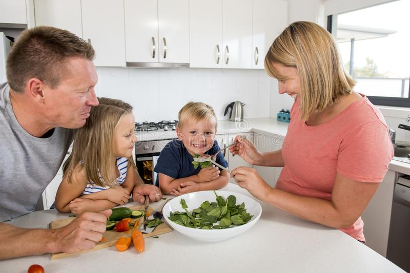 Young attractive couple mother and father preparing salad together with little son and young beautiful daughter in healthy vegetab stock photos
