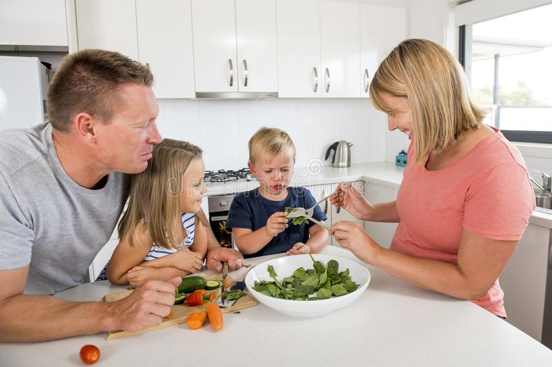 Young attractive couple mother and father preparing salad together with little son and young beautiful daughter in healthy vegetab stock image