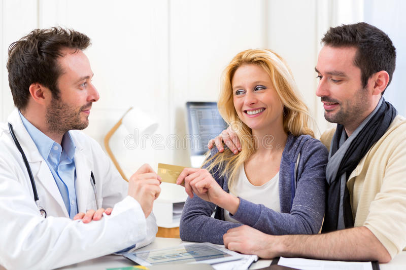 Young attractive couple paying consultation to the doctor. View of a Young attractive couple paying consultation to the doctor royalty free stock photos