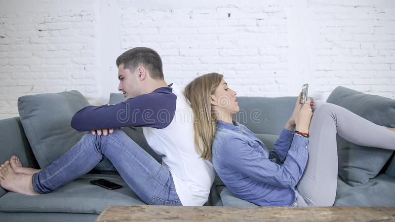 Young attractive couple in relationship problem with internet mobile phone addiction girlfriend ignoring sad neglected and bored b. Oyfriend at home couch men stock image