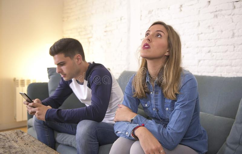 Young attractive couple in relationship problem with internet mobile phone gambling addict boyfriend ignoring sad neglected and bo. Red girlfriend at home couch stock photos