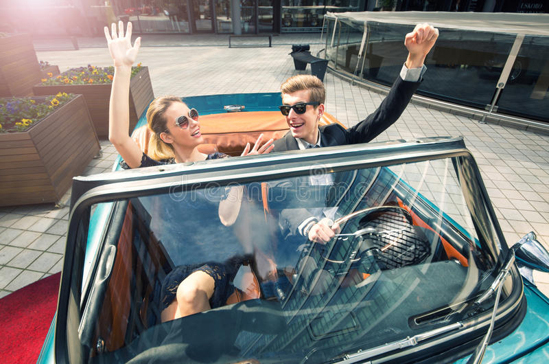 Young and attractive couple sitting in a luxurious retro car royalty free stock photos