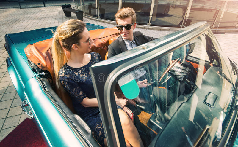 Young and attractive couple sitting in a luxurious retro car royalty free stock image