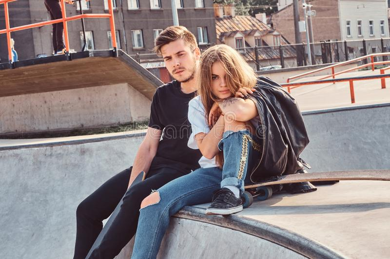 Young attractive couple of students are sitting at skatepark with their longboards stock image