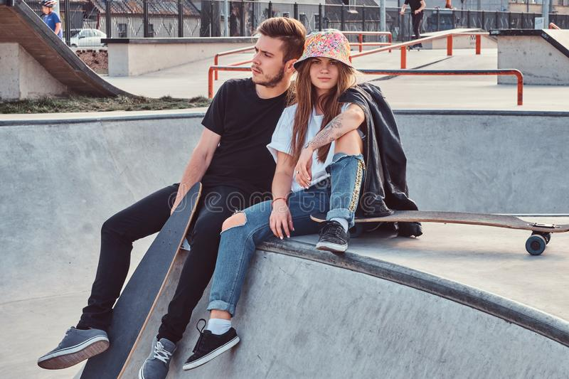 Young attractive couple of students are sitting at skatepark with their longboards stock photos